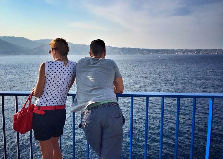 Rear View Of Couple Standing By Railing Of Ferry On Sea Against Sky