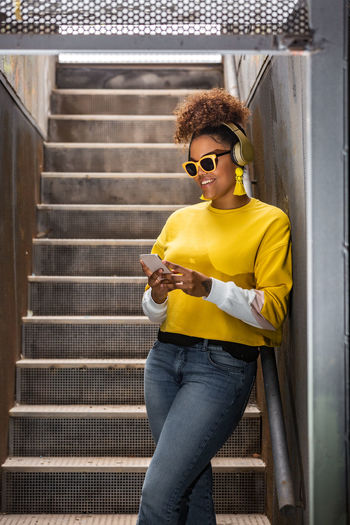 Young woman wearing sunglasses holding mobile phone standing outdoors
