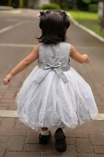 Rear View Of Little Girl Wearing Frock While Walking On Footpath