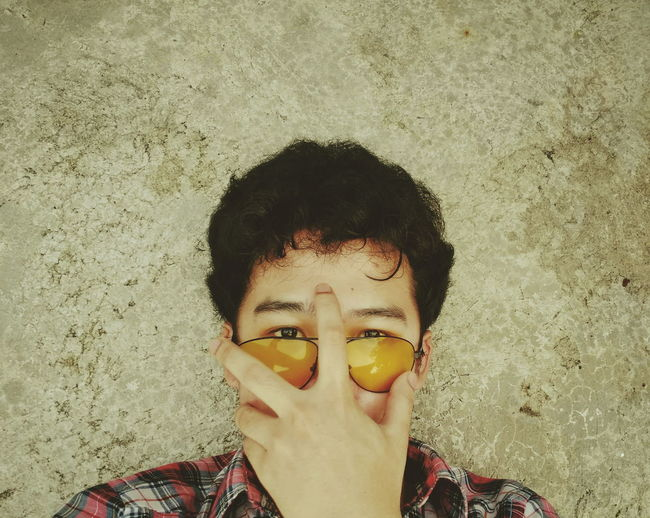 Portrait of boy wearing sunglasses against wall