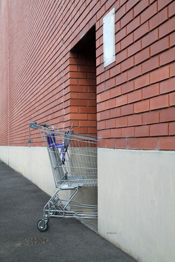 View of shopping trolley abandoned in brick building doorway