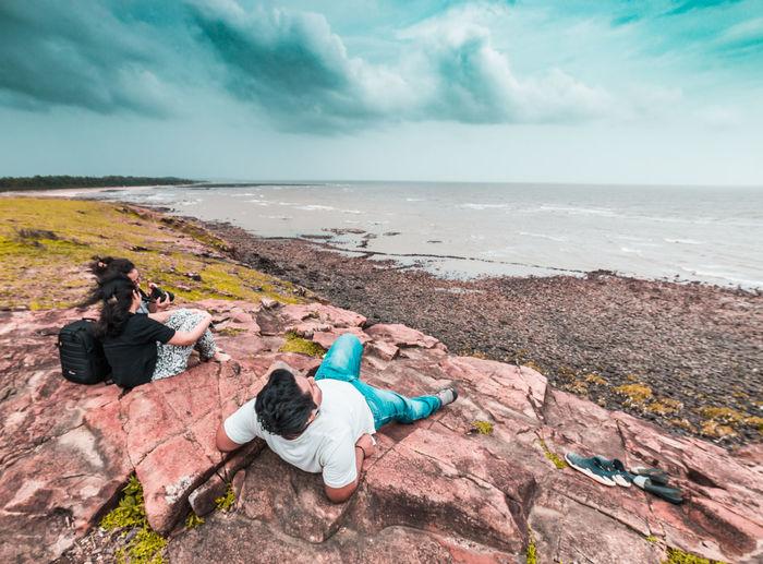 People on rocks by sea against sky