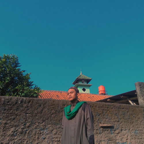 Low angle view of woman standing against building against clear blue sky