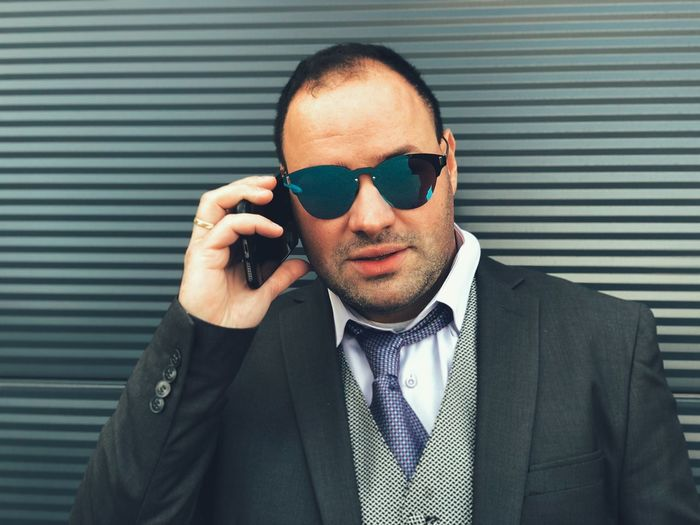 Portrait of businessman in sunglasses talking on mobile phone against wall