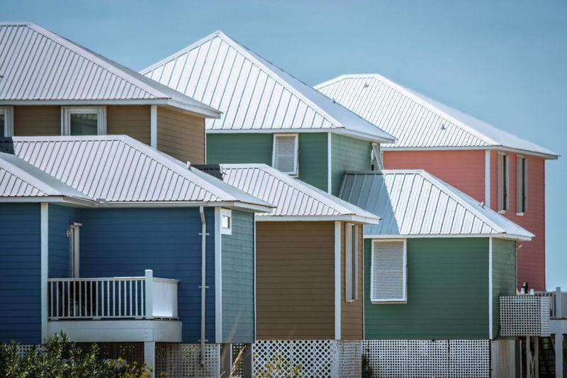 Houses in sea against buildings against clear blue sky