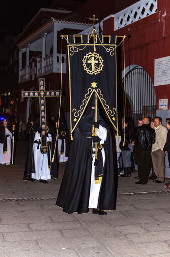 Puerto de la Cruz, Spain, 03/25/2016 - Traditional Holy Week processions (Easter). In the streets of Puerto de la Cruz Semana Santa Procession of the brotherhoods at night. Crucifixion Parish Way Of The Cross Church Catholic God Jesus Christ Holy Belief Christianity Spirituality Puerto De La Cruz Religion Catholic Holiday Holy Week Church Festival Holiday Lent Resurrection Penance Penitential Pilgrim Crucifix Brotherhood Semana Santa SPAIN Crowd Tradition Tenerife Teneriffa