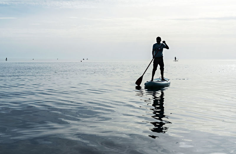 Young man on stand up paddle board on sea on sunny summer day, active lifestyle, outdoor activity
