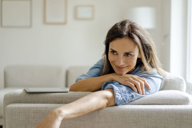 Portrait of woman sitting on sofa at home
