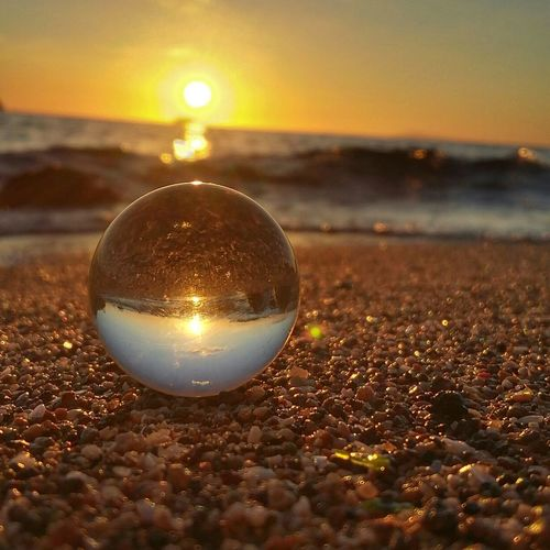 Close-up of ball on beach during sunset