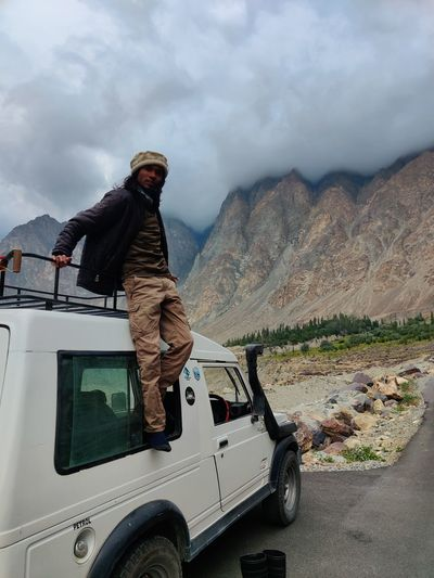 Side view of man on car against mountain range
