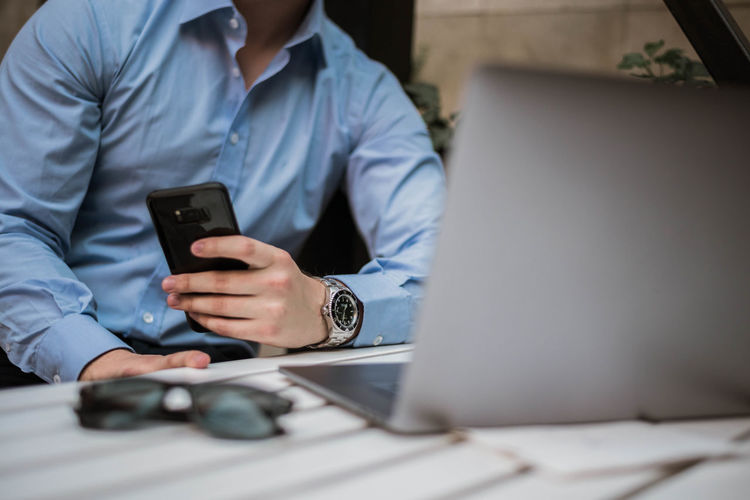 Midsection of businessman using mobile phone on desk