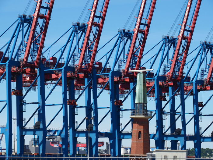 Cranes at harbor against blue sky