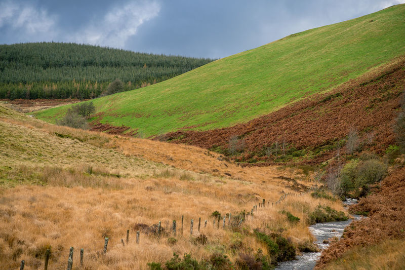 Stream Flowing On Mountain Against Cloudy Sky