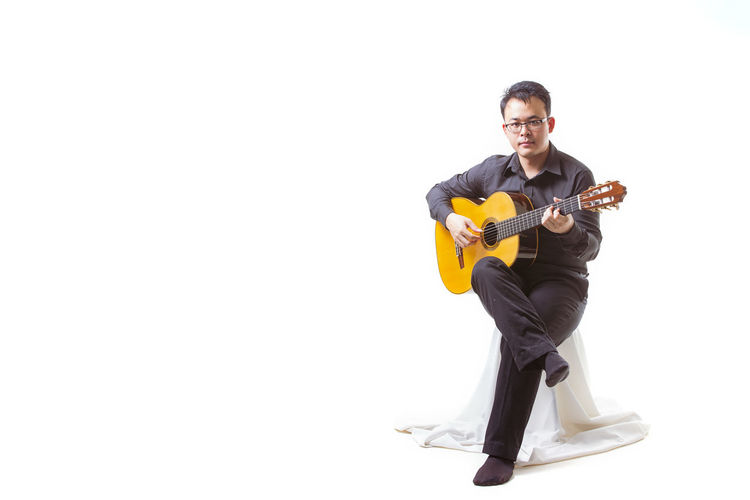 Full length of man playing guitar against white background