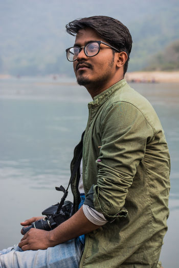 Young man wearing eyeglasses sitting with camera against sea