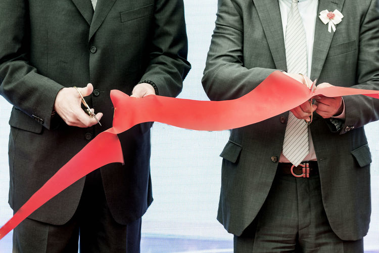 Midsection Of Businessmen Cutting Ribbon