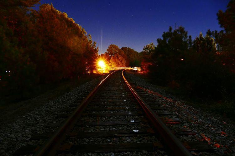 Railroad tracks amidst trees against sky at night