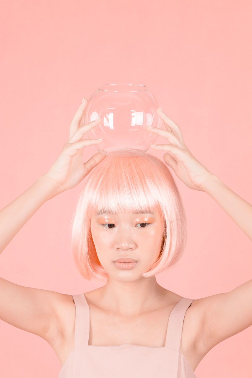 Thoughtful Woman With Dyed Hair Holding Jar Against Wall