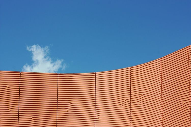 Low Angle View Of Patterned Wall Against Blue Sky