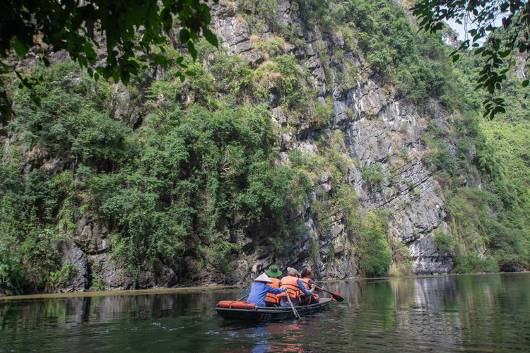 tourist sitting on boat at Trang An, Ninh Binh, Vietnam. Tree Water Nautical Vessel Plant Transportation Real People Mode Of Transportation Day Waterfront Group Of People Lifestyles Leisure Activity Nature River Men People Adult Togetherness Sitting Outdoors