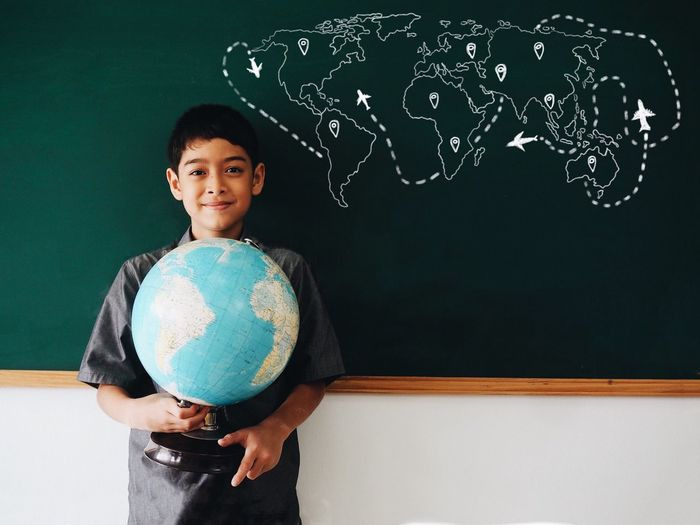 Portrait of boy holding globe while standing against blackboard in classroom