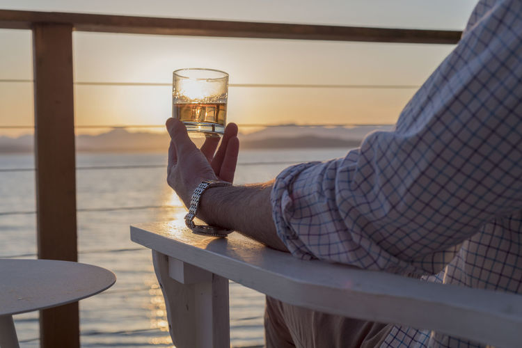 Professional businessman holding alcoholic drink on sea view deck at sunset Beach House Lifestyle Wristwatch Alcohol Bourbon Cruise Drink Food And Drink Glass Glass - Material Hand Holding Leisure Activity Lifestyles Luxury One Person Outdoors Real People Refreshment Rocks Sailing Sunset Water Wealth Whiskey