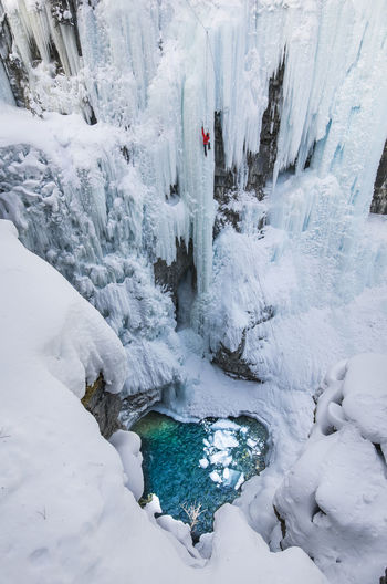 High angle view of woman climbing on snowcapped mountain during winter