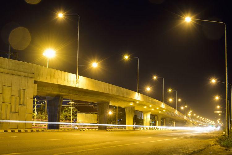 Illuminated bridge against sky at night