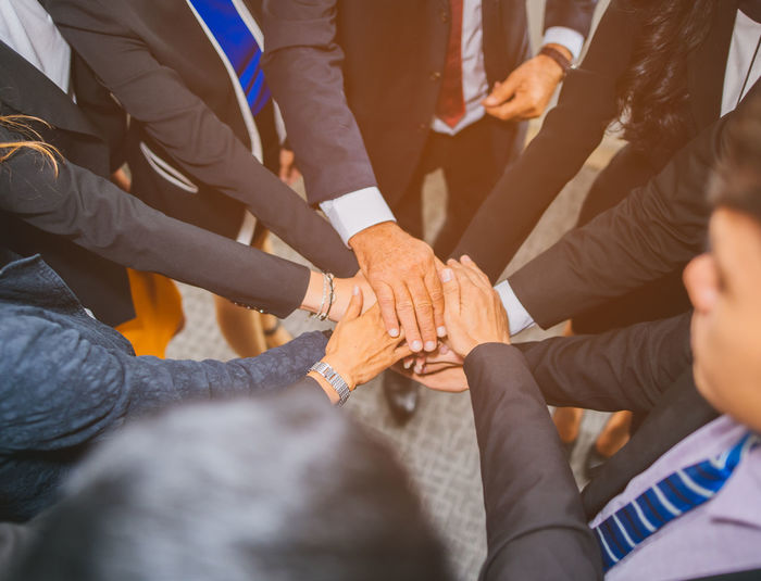 High angle view of business people stacking hands