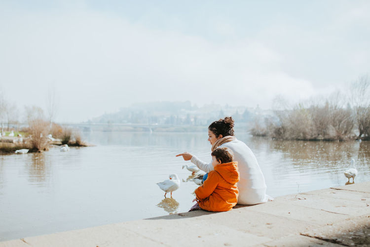 Mother with daughter sitting at lakeshore against sky