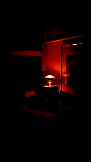 Man and illuminated lamp in darkroom
