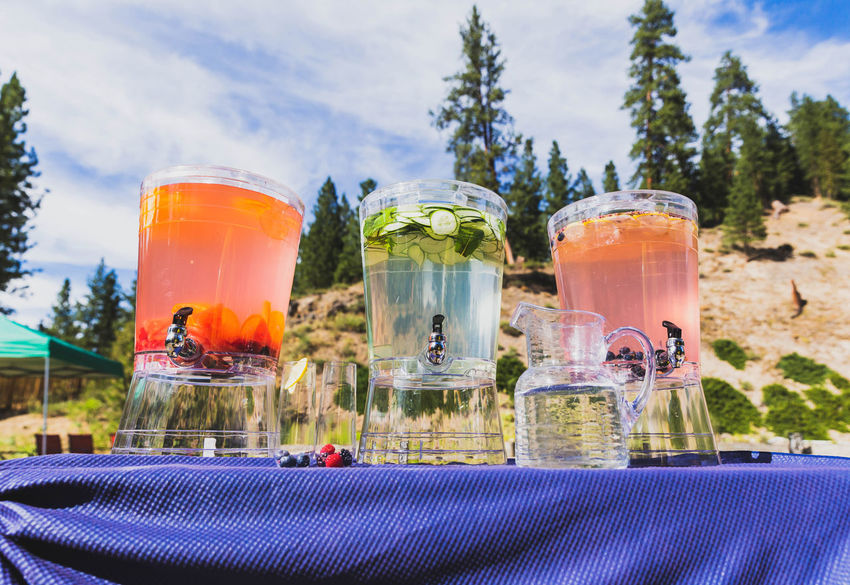 Three pitchers of fruit beverages sit on top of a table with a forested mountain in the background. Alcohol Close-up Cocktail Container Day Drink Drinking Glass Focus On Foreground Food Food And Drink Freshness Glass Glass - Material Household Equipment Luxury Nature No People Plant Refreshment Sky Table Transparent
