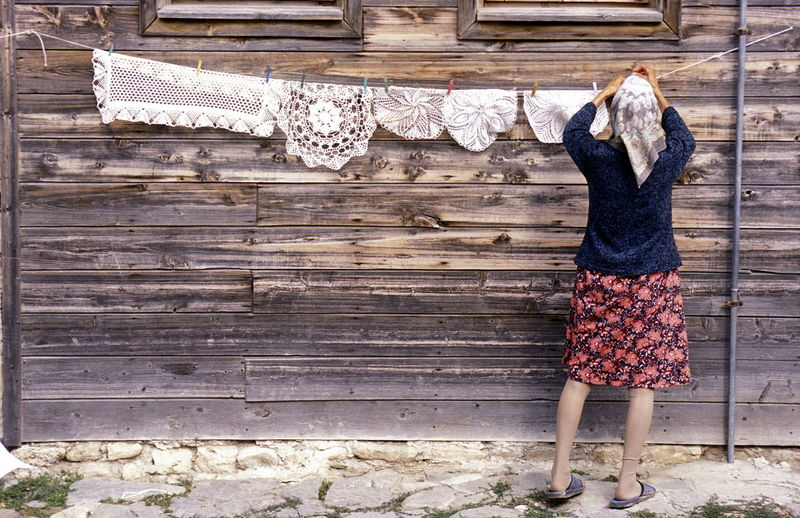 Rear view of woman drying place mats against house