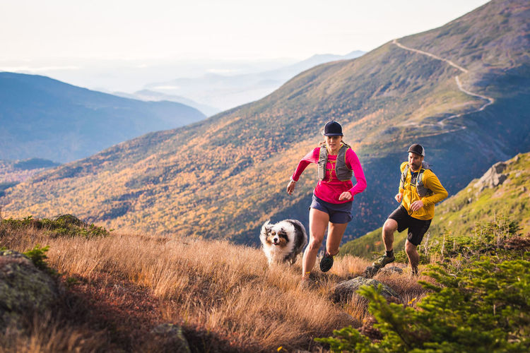 People with dog on mountain against sky