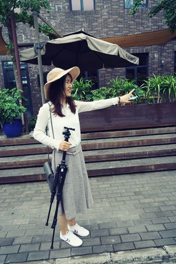 Woman with umbrella standing against brick wall
