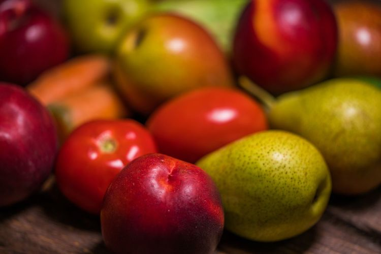 Close-up of apples with tomatoes and pears on table