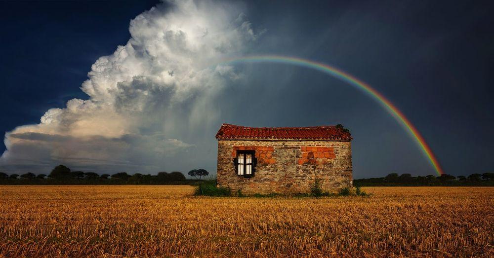 House on field against rainbow in cloudy sky