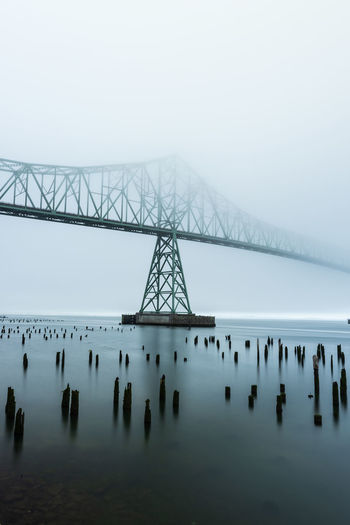 Low angle view of bridge over river during foggy weather