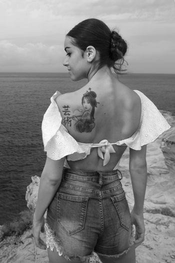 Rear view of young woman with tattoo on back at beach against sky