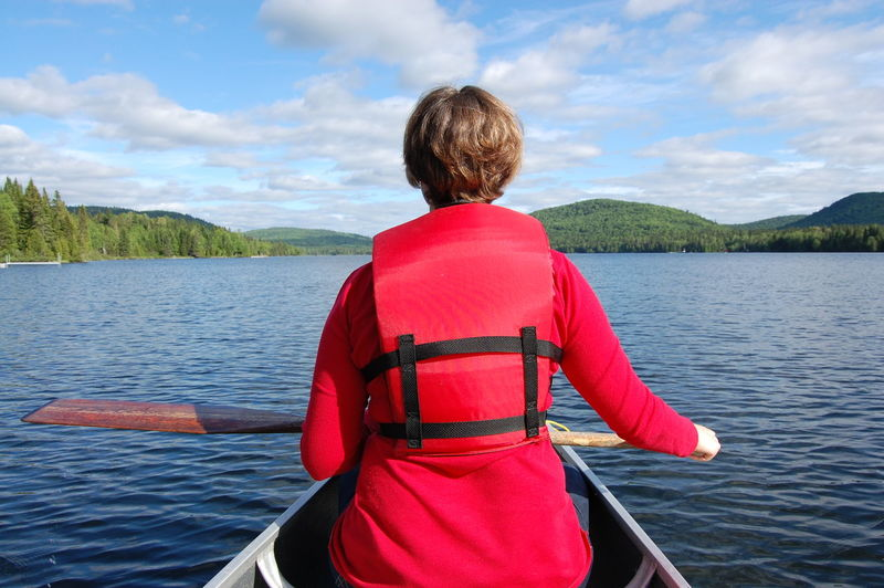 Rear View Of Woman Canoeing In River