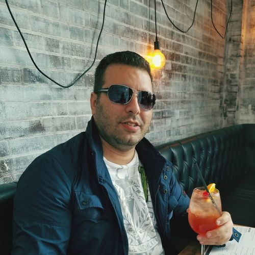 Portrait of man holding juice while sitting on sofa