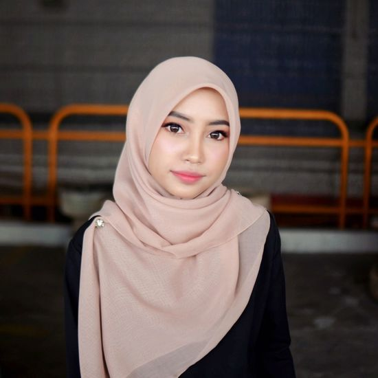Portrait Of Beautiful Young Woman In Hijab Against Blurred Background