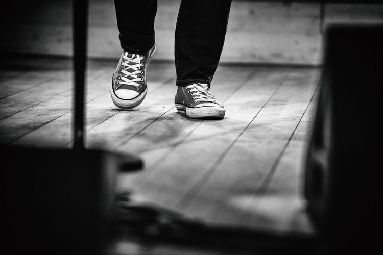 Low Section Of Man Wearing Canvas Shoes Walking On Floorboard