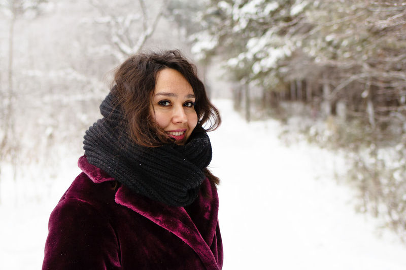 Smiling woman with long brown hair in a coat from faux fur on a background of winter forest.