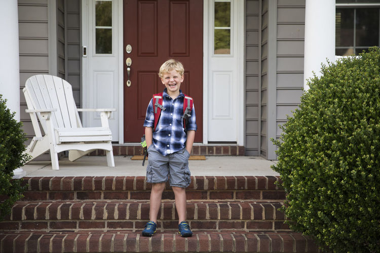 Portrait of smiling boy outside house against building