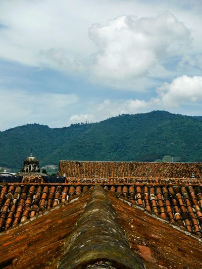 Panoramic View Of Roof And Mountains Against Sky