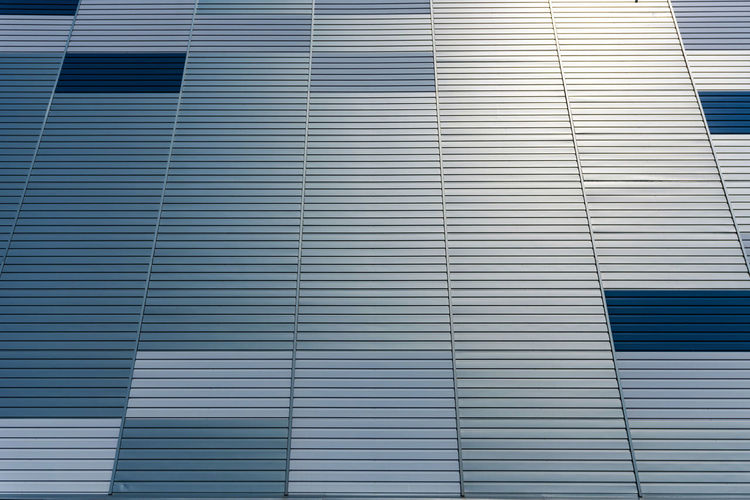 Abstract architectural background from modern buildings facade with blue and silver lines - image No People Backgraund Wallpaper Pattern Texture Architecture Close-up Details Full Frame Built Structure Building Exterior Day Outdoors Modern Metal Warehouse Cladding Façade Exterior Steel Modern Construction Structure Wall Building Surface Panel Design Material Metallic Business Industrial Silver  Painted Detail Plate Industry Blue Aluminium Urban Composite City Development Estate Lines Futuristic Iron Front View Style