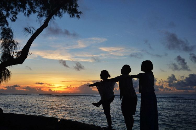 Silhouette female friends at beach during sunset