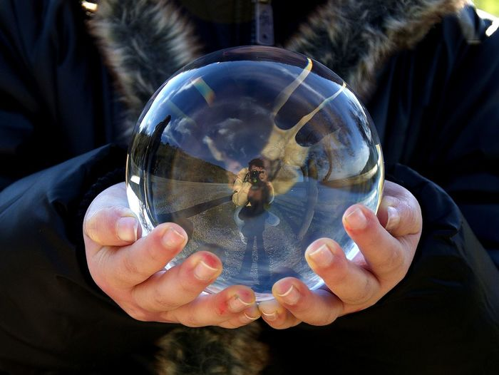 Midsection of woman holding crystal ball with reflection of man