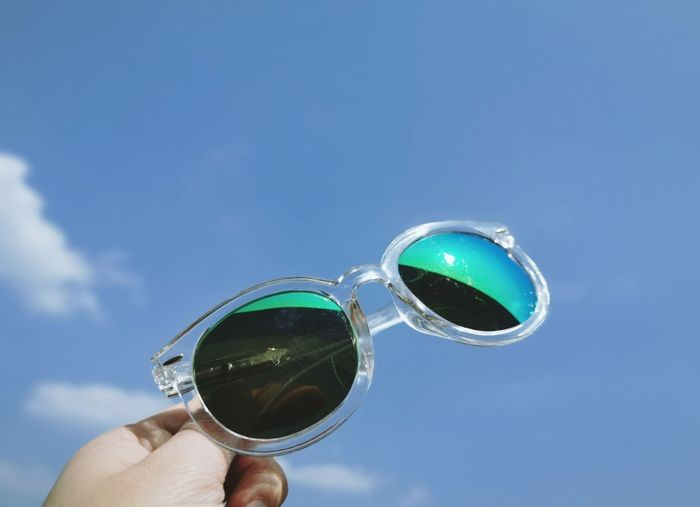 Cropped image of hand holding sunglasses against sky